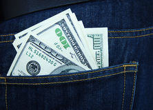 American dollars, hundred-dollar notes, sticking out of the blue jeans pocket. Royalty Free Stock Photos