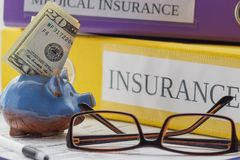 American dollars, insurance form, folders, pen, piggy bank and glasses Stock Photography