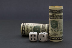 American dollars next to white and black dice depict risk and ch Stock Photography