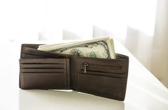 American dollars pack in the brown leather wallet. Laying on white table Royalty Free Stock Photography