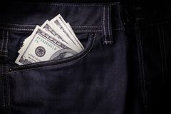 American dollars sticking out of the dark blue jeans pocket. Banknotes of a hundred dollars peep out of the pocket of jeans trousers Royalty Free Stock Photo
