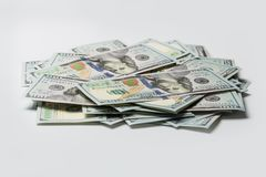 Stack of hundred dollars on white stock images