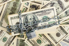 American dollars wrapped in chain. Stock Photo