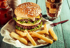 American double cheeseburger with French fries. American double cheeseburger on a sesame bun served with crisp golden French fries, a soda or soft drink and Royalty Free Stock Photography