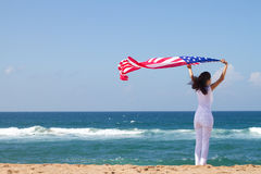 American dream. Concept: young woman holding a USA flag on beach stock images