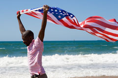 American dream. Young african american man running with USA flag on beach, american dream concept Stock Image