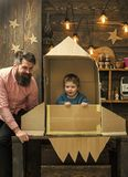 American dream. Boy play with dad, father, little cosmonaut sit in rocket made out of cardboard box. Child cute boy play. Cosmonaut, astronaut royalty free stock photos