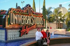 The american dream. A family, possibly of hispanic origin, poses for the photo, sitting in a fountain with the universal studios hollywood, ca logo in the Stock Photo