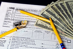 Broken pencil on income tax form. Hundreds of dollars and busted pencil on a tax form stock images