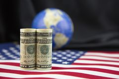 American economic policy encompasses global trade. Focus on American currency placed on national flag with unfocused black satin and globe background in shallow Stock Photos