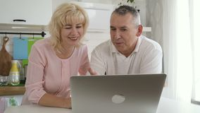 American elderly couple is talking, sitting at kitchen desk with laptop. Mature senior and woman love online shopping, using pc at home. Smiling old people stock footage