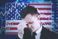 American entrepreneur with declining finance graph. American entrepreneur looks stressed with declining finance graph and American flag in the trade stock Royalty Free Stock Photo