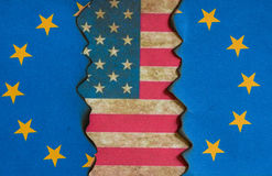 American European fracturing flag concept. American flag behind fracturing European flag background Royalty Free Stock Images