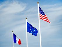 Flags of America, Europe Union and France on flagpole. American, European union and French flags on flagpole waving over blue sky Stock Images