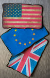 American, European and United kingdom flags. On brushed metal background Stock Photos