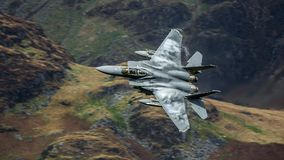 American F15 fighter jet aircraft. United States Air Force USAF F15 military fighter jet aircraft against British mountain backdrop whilst on a low level royalty free stock photo