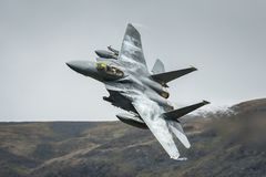 American F15 fighter jet aircraft. United States Air Force USAF F15 military fighter jet aircraft against British mountain backdrop whilst on a low level stock image