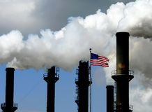 American Factory. Chimney stacks from factory with steam and smoke and American flag stock photo
