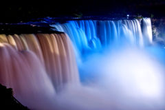 American Falls at Niagara. The American Falls of Niagara appear drenched in reddish and blueish lights on a beautiful evening Royalty Free Stock Image