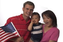 American family. American husband with Japanese wife and there baby, holding the American flag for 4th of July stock photos