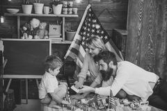 American family and cute son play with usa flags. Parents teaching son american traditions playing, enjoy parenthood. Kid with parents play with plastic blocks Stock Photo