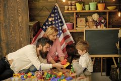 American family and cute son play with usa flags. Parents teaching son american traditions playing, enjoy parenthood. Kid with parents play with plastic blocks stock photos