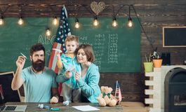 American family at desk with son making paper planes. Homeschooling concept. Kid with parents in classroom with usa flag. Chalkboard on background. Parents Royalty Free Stock Photos