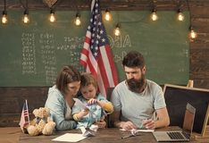 American family at desk with son making paper planes. Homeschooling concept. Parents teaching son to create, handmade. Kid with parents in classroom with usa stock photo