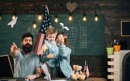American family at desk with son making paper planes. Homeschooling concept. Parents teaching son american traditions. Playing. Kid with parents in classroom Royalty Free Stock Image