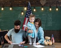 American family at desk with son making paper planes. Kid with parents in classroom with usa flag, chalkboard on. Background. Parents teaching son american Stock Photo