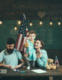 American family at desk with son making paper planes. Parents teaching son american traditions playing. Kid with parents. In classroom with usa flag, chalkboard Stock Images