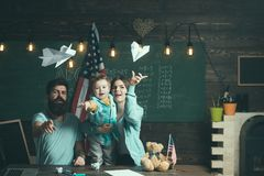 American family at desk with son play with paper planes. Homeschooling concept. Kid with parents in classroom with usa. Flag, chalkboard on background. Parents Royalty Free Stock Photos