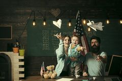 American family at desk with son play with paper planes. Homeschooling concept. Kid with parents in classroom with usa. Flag, chalkboard on background. Parents royalty free stock photography