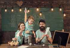 American family at desk with son play with paper planes. Homeschooling concept. Parents teaching son american traditions. Playing. Kid with parents in classroom stock photo