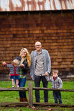 American Family of Four Lifestyle Portrait. Family lifestyle portrait of a mother, father, son and daughter in front of a rustic barn in the country Stock Photos
