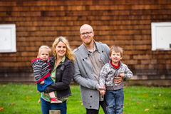 American Family of Four Lifestyle Portrait. Family lifestyle portrait of a mother, father, son and daughter in front of a rustic barn in the country Royalty Free Stock Photography