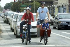 American family rides bicycles. Sannyvale, California, United States - February 20, 2016: Father, mother and son riding bicycles on the roadway. Son sits in a Stock Images