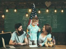 American family sit at desk with son and usa flag. Kid with parents in classroom with usa flag, chalkboard on background. Patriotic education concept. Parents Stock Photos