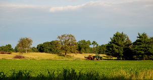 American Farm. This is a photo of a farmer on a tractor  and some of the property around it Royalty Free Stock Images