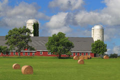 American Farm. With red barn, white silos, green meadow, and hay rolls on green field in Maryland, USA Royalty Free Stock Photo