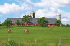 American Red Farm. With red barn, silos, green meadow, and hay rolls on green field and Barbed wire wooden fence in rural Maryland Stock Image