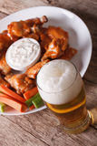 American fast food: buffalo wings and beer close-up vertical. American fast food: buffalo wings with sauce and beer on the table close-up vertical stock photos