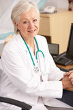 American female doctor sitting at desk Stock Image