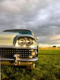 American - Fieldtrip. Closeup of the rainy front of a classic american car from the 1950 parked under a dark and cloudy sky Stock Photography