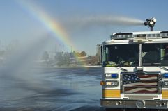 American fire truck. Spraying high pressure water creating a rainbow Stock Photography