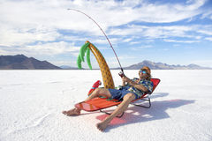 American Fisherman Goes on Cheap Ice Fishing Vacation Holiday. Redneck American fisherman wearing Hawaiian shirt goes on cheap ice fishing vacation holiday with stock photo