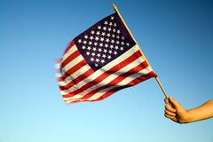 American Flag. Child holding small US flag on the wind outdoor Stock Photo
