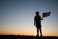 American Flag. Young boy holding an American flag at sunset Royalty Free Stock Photo