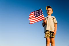 American Flag. Young boy holding an American flag on a blue background of a clear sky Stock Photo