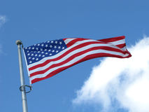 American flag. Low angle view of American flag flying in breeze with blue sky and cloudscape background Stock Images